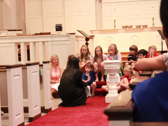 Children listen to the Rev. Sharon Junn, associate pastor, at the back-to-school prayer service held by First Presbyterian Church on Wednesday.