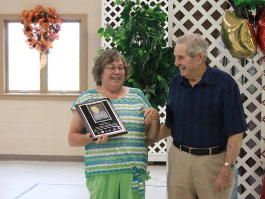 Linda Kauffman shows Robert Jones a plaque at his 102nd birthday party Sunday at the South Jackson Community Center.
