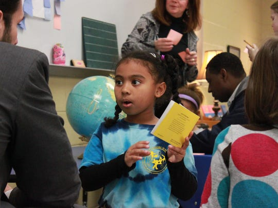 Kindergarten student Jo-Hannah Ross reads a book to City Councilman Scott Conger on Friday at the Montessori School at Bemis.