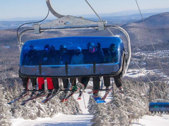 "Skiers wave from a ""bubble chair"" on Mount Snow Resort's Bluebird Express Lift."
