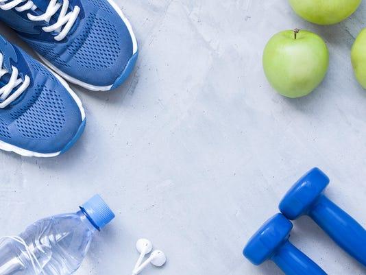 Flat lay sport shoes, dumbbells, earphones, apples, bottle of water