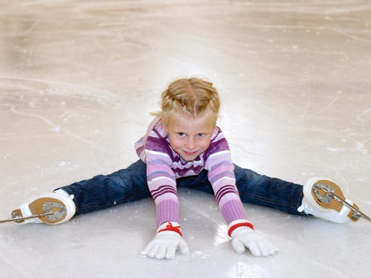 The little girl sitting on ice in ice skating.