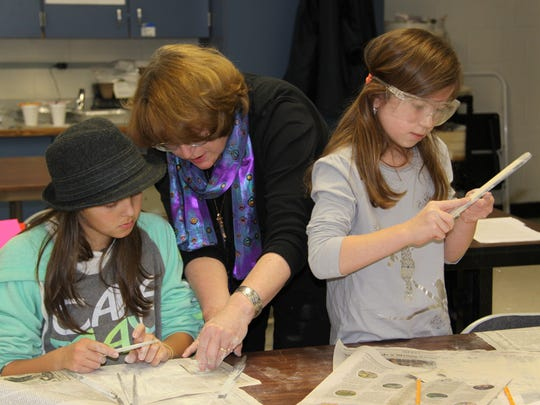 Volunteer Karen Rakoski, center, works with Hill School students Lauren Dailey, left, and Ava Nicolo, during Ro-Ro Rocks and Minerals Club, which she runs.
