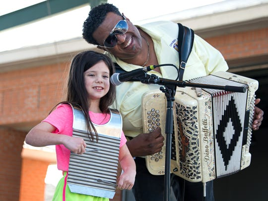Grammy-winning musician Chubby Carrier, right, plays with a young fan at the 2016 Zydeco Marathon at Parc International.