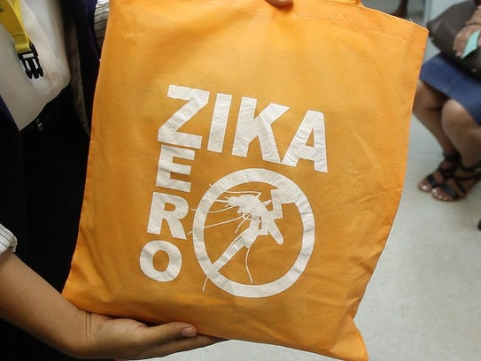 A Zika counselor holds up a Zika kit she is about to