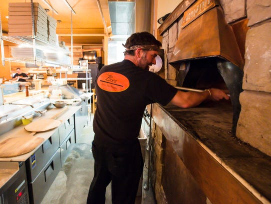 Peter Grimard cooks a pizza supreme at La Boca Wood