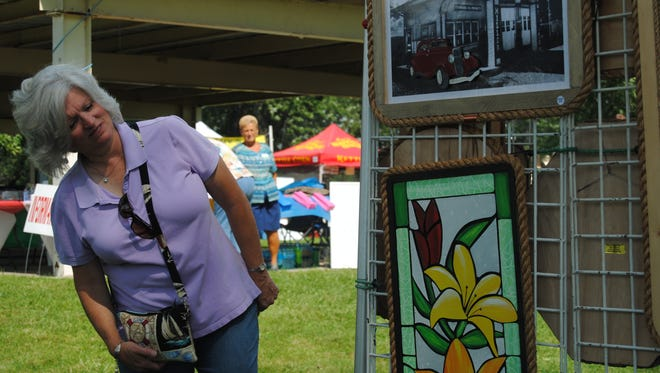 Marine City resident Cindy Kongabel looks over pieces in the booth of Dave and Carol Diem on Saturday, Aug. 20, 2016, during Art in the Park in Marysville. For Kongabel, the event was a family affair.