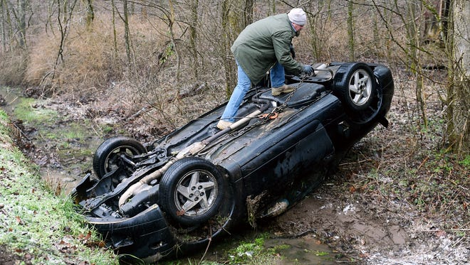 Joe Anglin with Grace Towing pulls a car out of a ditch on Johnson Hollow Road in Williamson County after the driver lost control of his car on the icy road on Wednesday.