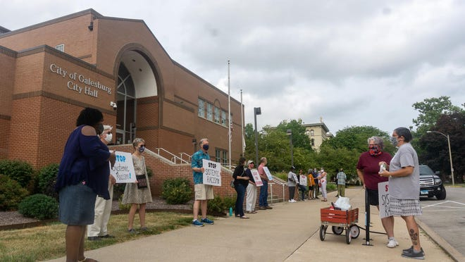 FILE: Supporters of the NAACP rally stand in front of Galesburg City Hall.