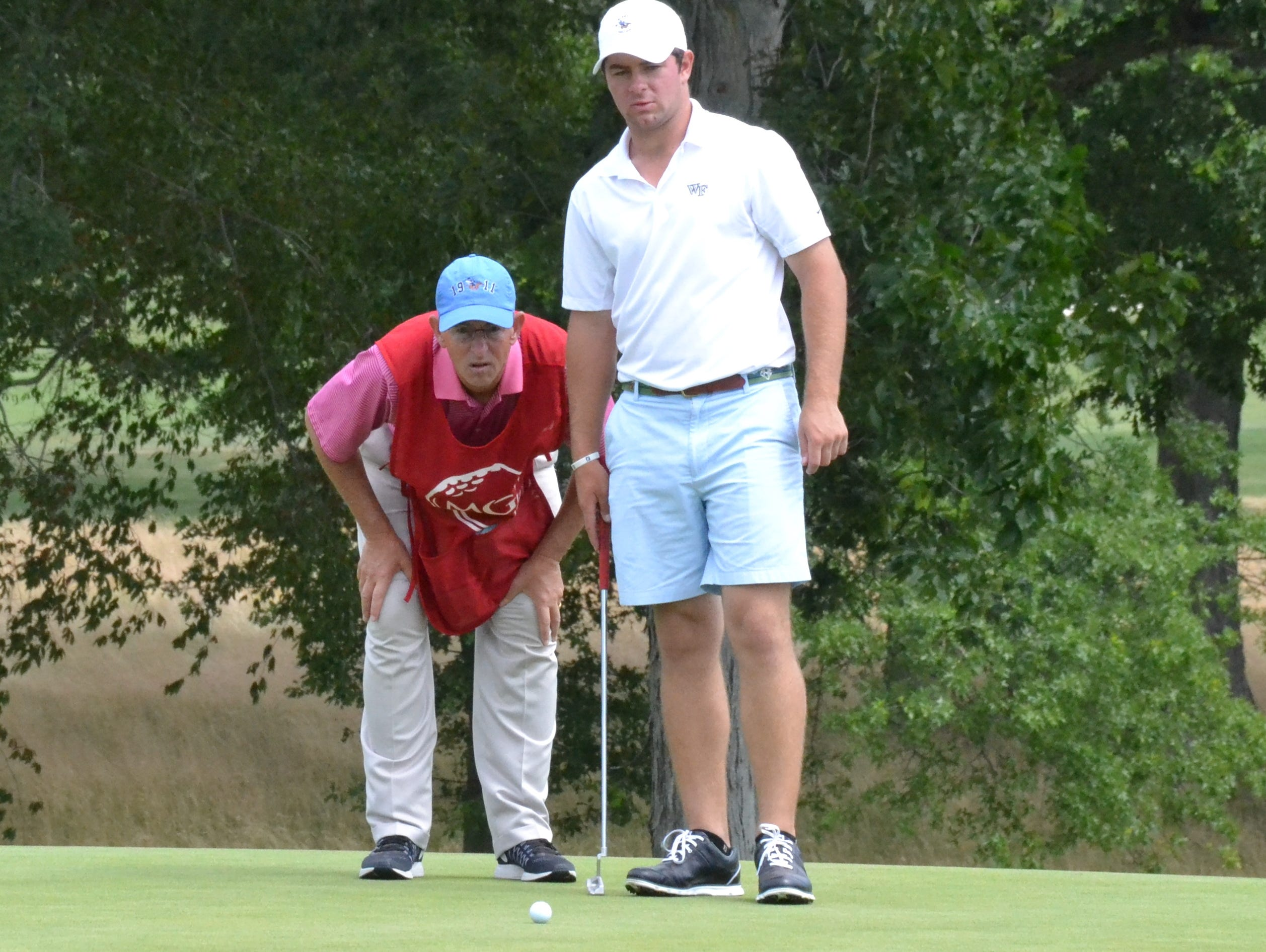 Cameron Young looks over a putt Monday during the first round of the Ike Championship while his father, Sleepy Hollow C.C. head pro David Young gets a closer look. The defending champion opened with an even-par 71 and is eight shots off the lead.