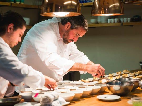 Chef Kevin Binkley grates a perigord truffle over a