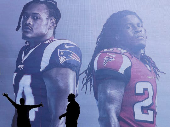 Poeple pose with a sign at the NFL Experience ahead of the NFL Super Bowl 51 football game Friday, Feb. 3, 2017, in Houston. The New England Patriots will face the Atlanta Falcons in the Super Bowl Sunday. (AP Photo/Charlie Riedel)
