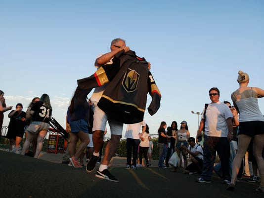 People take turns posing for photos with the NHL hockey expansion team Vegas Golden Knights' new jersey Tuesday, June 20, 2017, in Las Vegas. (AP Photo/John Locher)