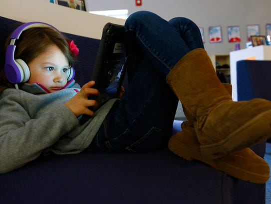 Harper Page, 5, listens to a story on her iPad on Monday. Odyssey has flexible seating options, and students can choose where to learn during independent study times.