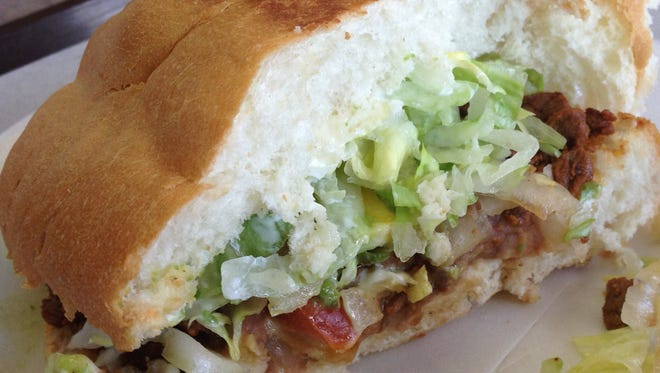 Half of a carne asada torta - a Mexican sandwich on bollio or French bread role - features tomatoes, lettuce, avocado, mayonnaise, refried beans and carne asada.