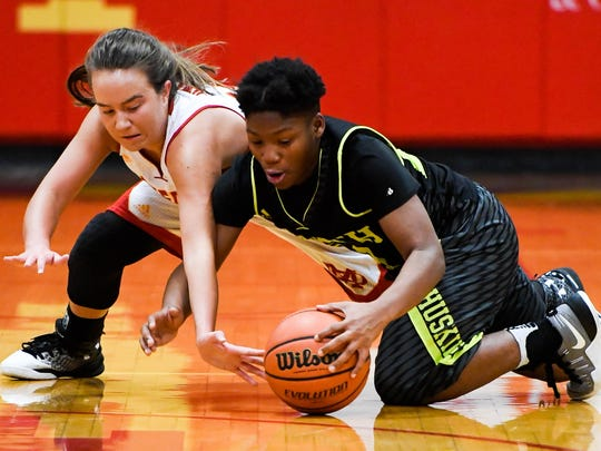Mater Dei's Ali Spahn and North's Fredrionna Adams scramble for a loose ball at mid-court as the Mater Dei Lady Wildcats play the North High Huskies at Mater Dei Wednesday, December 21, 2016.