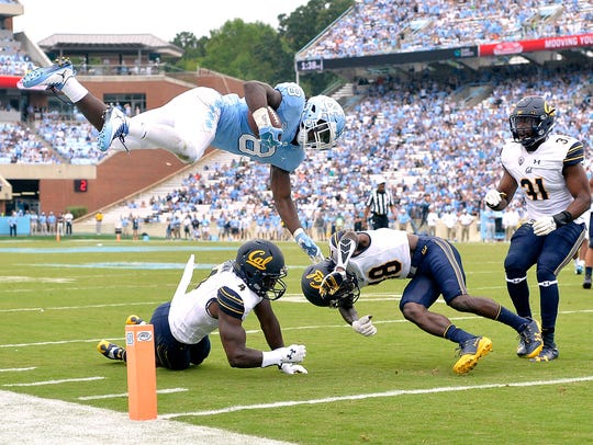 North Carolina running back Michael Carter hurdles