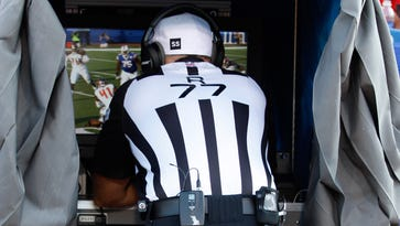 NFL referee Terry McAulay (77) assess a replay during a 2014 game.