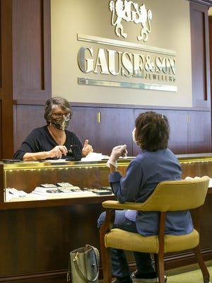 Sandi Barnett, manager at Gause & Son Jewelers, talks with a customer on Friday. The store doesn't require customers to wear masks, but employees must do so when working with customers. They also have masks on hand if a customer wants one. More than 500 doctors and other medical professionals have signed a letter asking both city and county officials to mandate face coverings.
