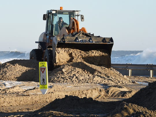 Rehoboth Beach Public Works Director Mike Peterman clears sand from Surf Avenue on Sunday morning. The blizzard that hit the region Friday evening triggered flooding in the area.