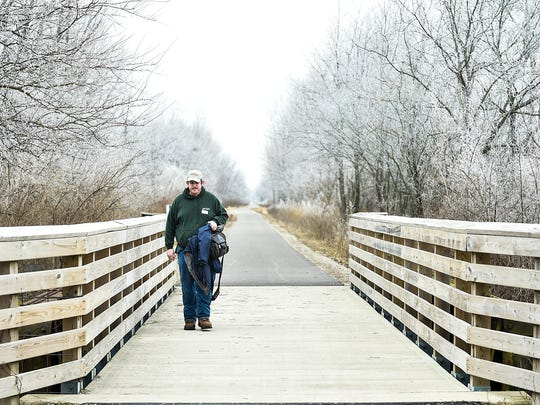 James Anderson, a Park Naturalist for the Marion County Park District, walks back to the Nature Center after checking on a family of beavers that are living in one of the lakes on the Tall Grass Trail.