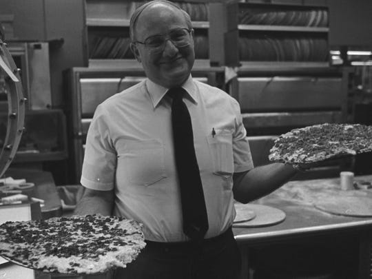 Arni Cohen, in this 1983 photo, shows off two of his famous pies from Arni's. The restaurant Cohen founded in 1965 was inducted into the Pizza Hall of Fame this week.
