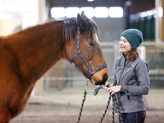 Equine Manager Elizabeth Karrmann works with Rufus