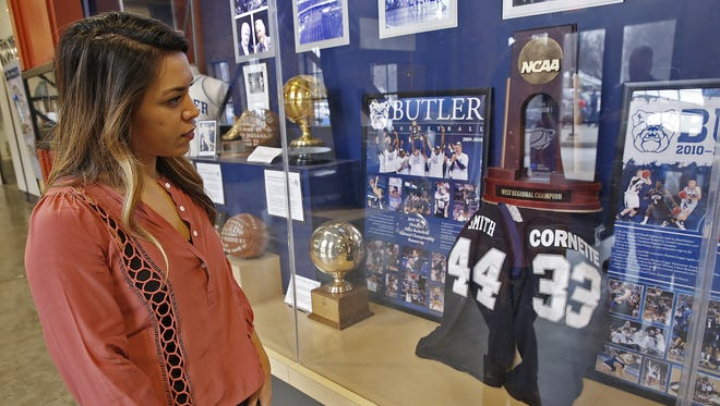 Samantha Smith looks at a Butler basketball history display, at Hinkle Fieldhouse, Monday, January 2, 2017, thinking of a year without her husband Andrew, who wore jersey #44.  Former Butler University basketball player Andrew Smith died January 12, 2016, after a long, public battle with non-Hodgkin lymphoma, and later leukemia.
