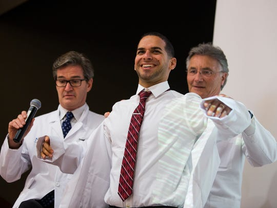 """Dr. Daniel Morales receives his white coat during the white coat ceremony on Monday, June 26, 2017, at the Telford Center Auditorium at the NCH Downtown Baker Hospital. """"They get a white coat with their name and then a beeper, and then their life changes,"""" said Dr. Charles Graeber, program director for the internal medicine residency."""