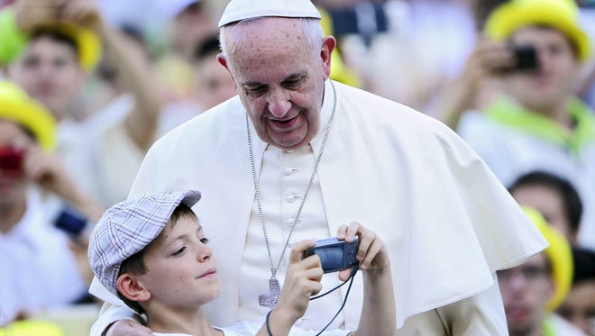 Pope Francis takes a photo with a child during a meeting with thousands of altar boys in St Peter's Square on Aug. 4, 2015.