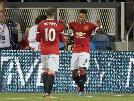 Manchester United midfielder Memphis Depay celebrates with forward Wayne Rooney after a goal against the Earthquakes during the first half at Avaya Stadium.