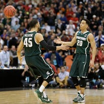 Denzel Valentine (45) celebrates with Travis Trice after MSU's 62-58 NCAA regional semifinal victory over against Oklahoma early Saturday in Syracuse, N.Y. Trice and Valentine combined to make six free throws in the final 1:19 to secure the win for the Spartans.