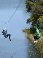 Claire Butler, 15, and Ceanna Potter, 14, of Wausau ride down together on the zip line at NEW Zoo Adventure Park in Suamico.