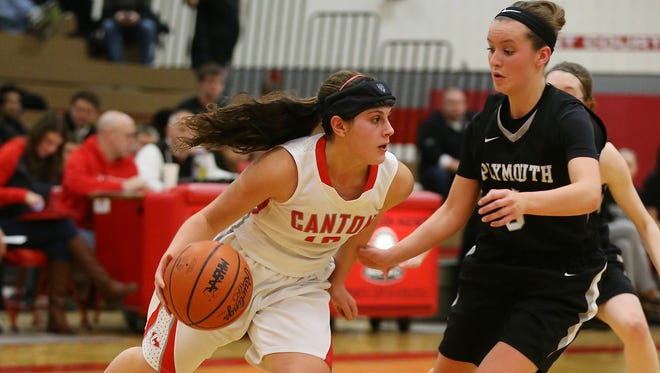 Canton's Alexa Lagola (No. 13) looks to dribble past Plymouth's Paige Slominski.