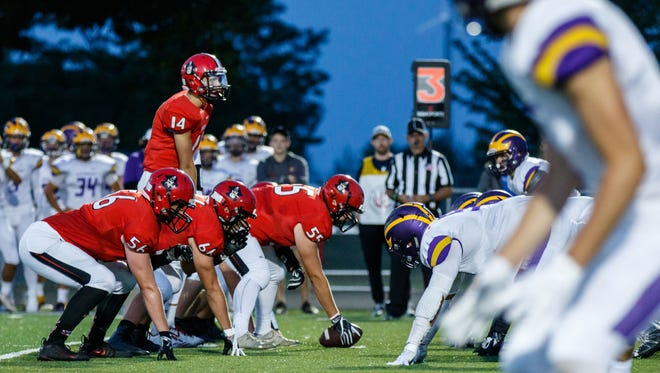 Pewaukee quarterback Josh Swanson (14) looks across the line during the game at home against New Berlin Eisenhower on Friday, Aug. 25, 2017.