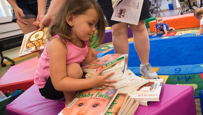 Kynsleigh Bachy, 2, picks out a book during a children's program at the Windsor Severance Library Friday in Windsor. Clearview Library District, which operates the library, is seeking to build a larger, $20 million facility on Main Street.