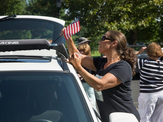 Eden Melmed of Wall decorates her car at Dorbrook Recreation area before joining the protestA small but dedicated group of protesters with Indivisible NJ 4th District drove their cars around the front of Trump National Golf Course in Colt Neck to protest President Trump and the current White House policies.