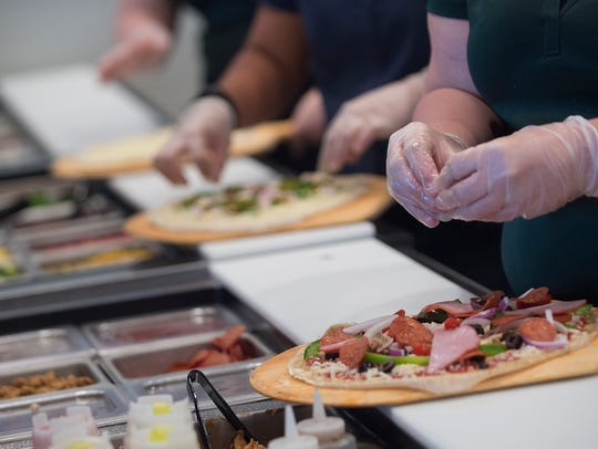 Employees make pizzas during a media event at the store