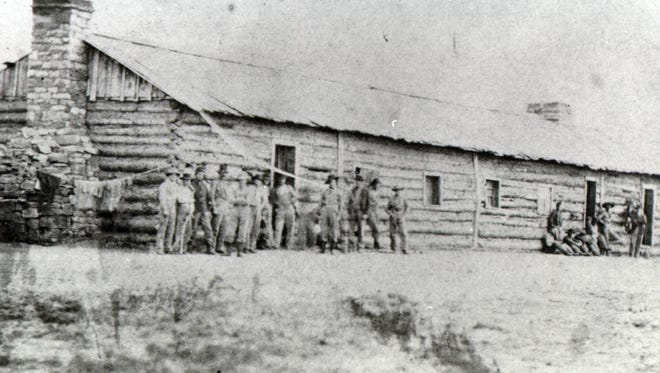 Soldiers stand in front of one of the barracks at Fort Collins in 1865.