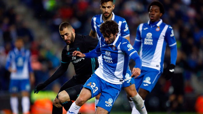 Real Madrid's Benzema, left, duels for the ball with Espanyol's Esteban Granero during the Spanish La Liga soccer match between Espanyol and Real Madrid at RCDE stadium in Cornella Llobregat, Spain, Tuesday, Feb. 27, 2018.