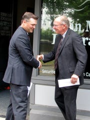 Henry Dunn II, left, president of Henry Dunn Insurance in Towanda, shakes hands with Swan Morss Insurance President Dan O'Connell on Tuesday. The pair announced a merger of the two longtime insurance agencies.
