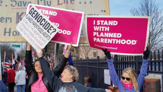 A Planned Parenthood supporter and opponent try to block each other's signs Feb. 11, 2017, during a protest and counter-protest in St. Louis.