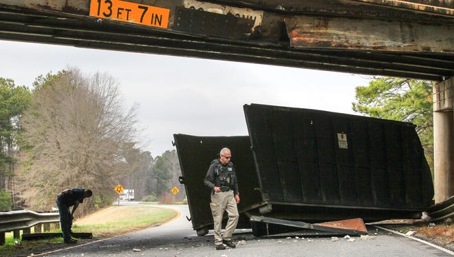 An Anderson County Environmental Services officer, right, walks by the driver of a truck, left, on Feb. 22, under the S.C. 20/U.S. 29 Connector bridge over U.S. 29 North near Williamston. The accident closed the bridge and northbound U.S. 29 for nearly a month.