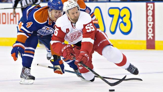 Detroit Red Wings defenseman Niklas Kronwall is tripped by the Edmonton Oilers' Taylor Hall on Oct. 21, 2015.