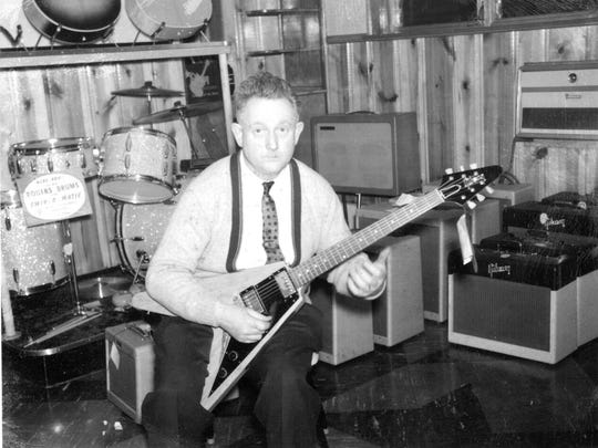 Former Indianapolis music Store owner Amos Arthur plays a 1958 Gibson Flying V guitar in a photograph taken for a store advertisement.