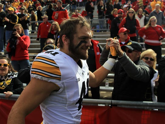 Iowa linebacker Bo Bower high-five's fans following