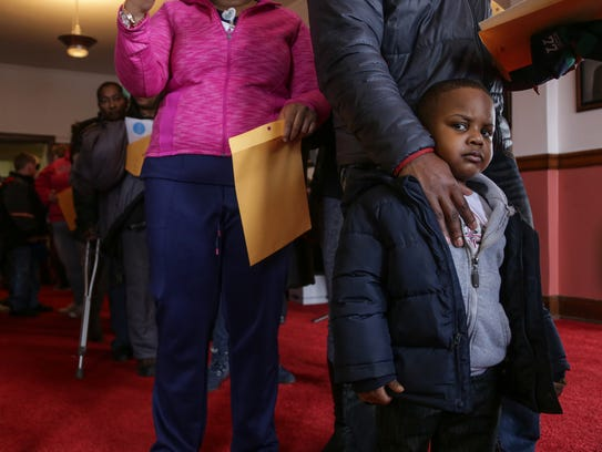Jaylen Smith, 4, of Flint waits in line with his father,