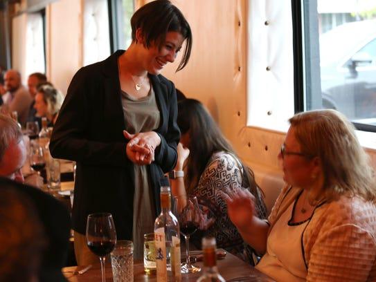Sommelier Rachel Van-Til talks to a guest at James