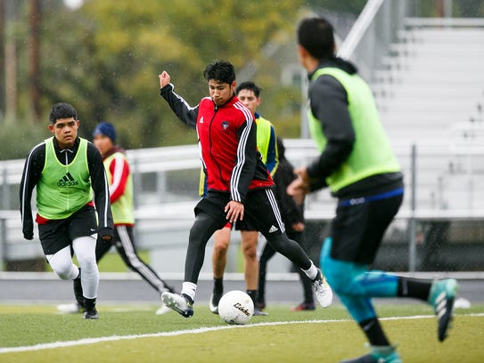 North Salem soccer player Alan Cruz, center, and teammates