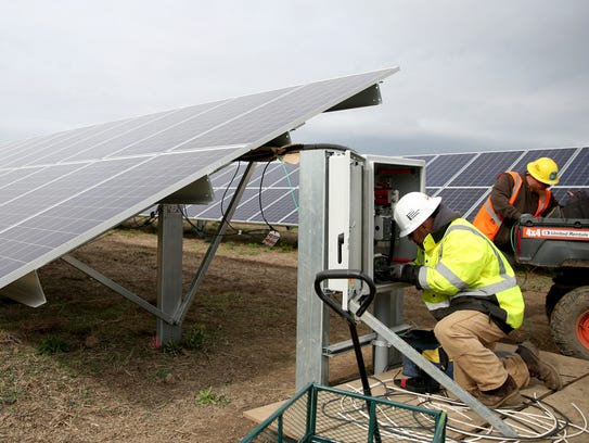 Electricians Ryan Lichty, left, of Silverton, and David Hammang, of Dayton, work on the Cypress Creek Renewables solar energy farm under construction just outside Silverton, Ore., on Tuesday, Oct. 17, 2017.